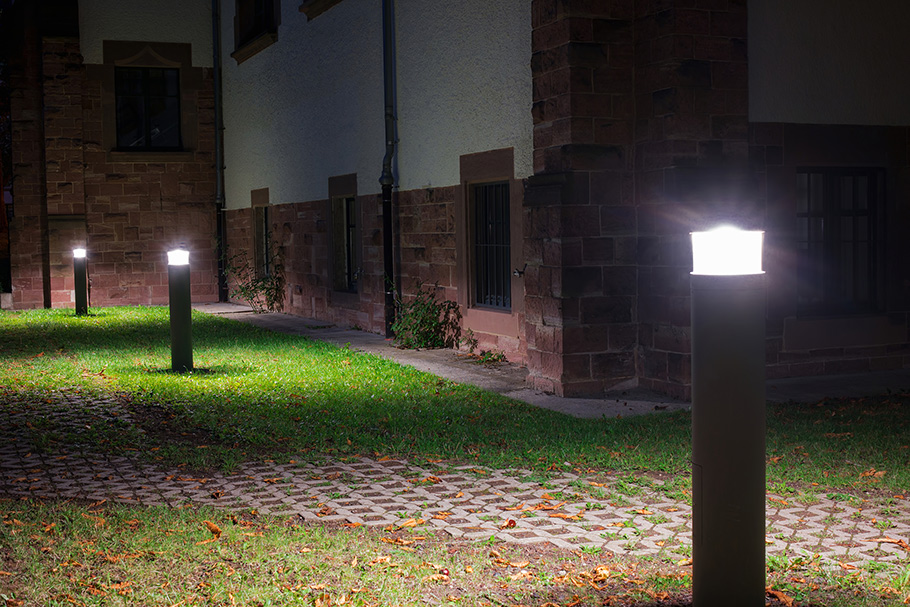 Beside a red brick campus building, three bollards light a dusty pathway
