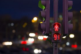 A don't walk symbol on a street light shows 91 seconds left on a timer, scene at night