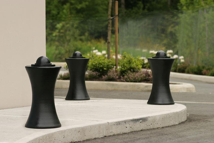 Three beautiful maritime bollards guard the corner of a sidewalk: plantings in the background