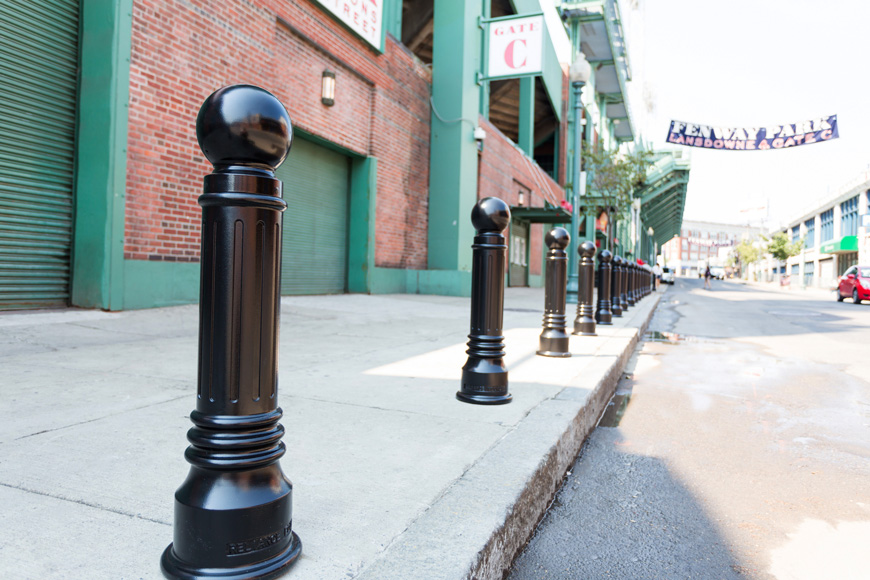 """A banner announcing """"FENWAY PARK"""" floats over a city street lined with bollards"""