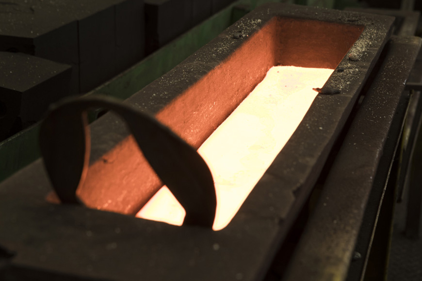 Glowing molten metal fills a sturdy metal form that will cool into an ingot