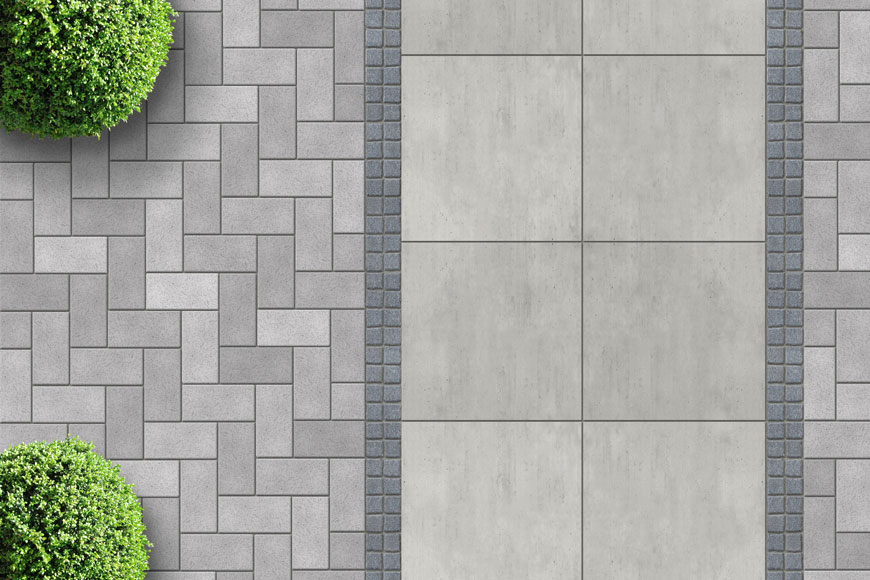 An aerial shot captures a top-down image of cobblestone pavers and bushes
