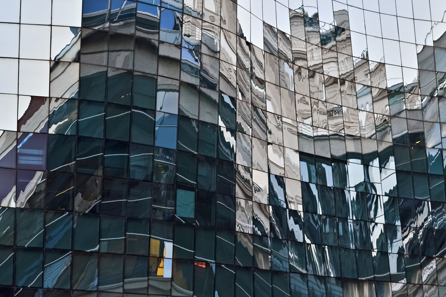 The warped glass of a building reflects an odd view of an old church