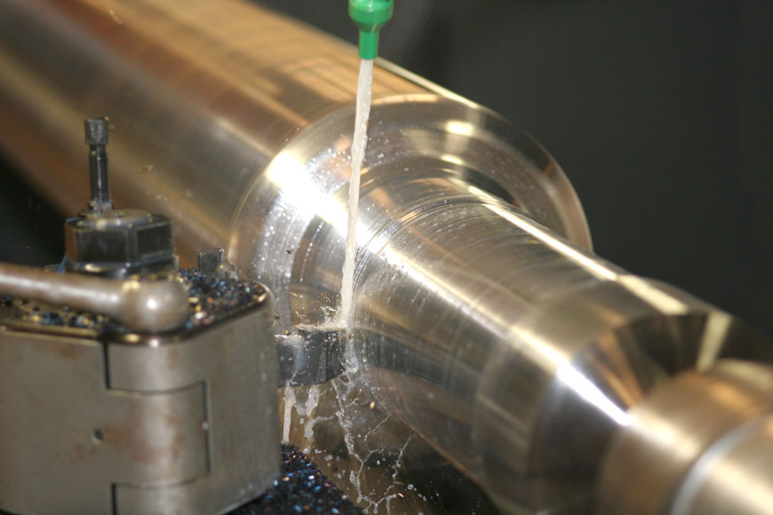 A pickled piece of stainless steel turns on a lathe that carves its diameter