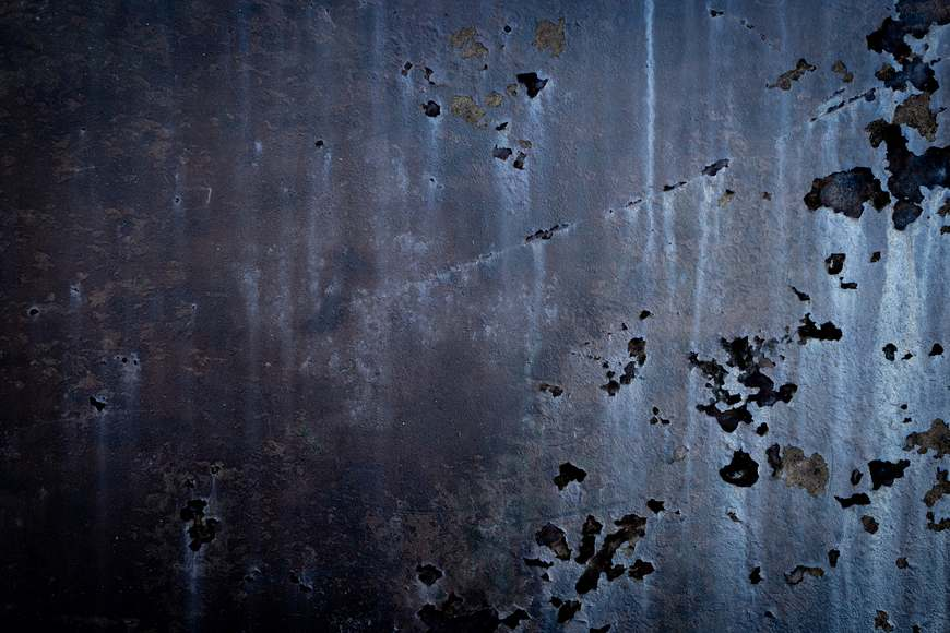 A sheet of metal has been eaten through with holes due to pitting corrosion