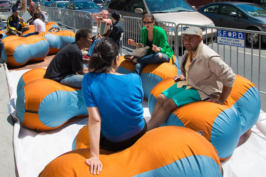 Adults interact on bean bags outdoors
