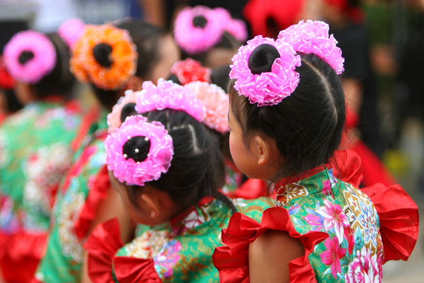 Dressed-up children with ruffled pink ties in their hair wait to perform a Lunar New Year dance.