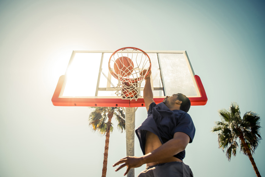A man leaps above the camera to dunk a basketball on a sunny court surrounded by palm trees.