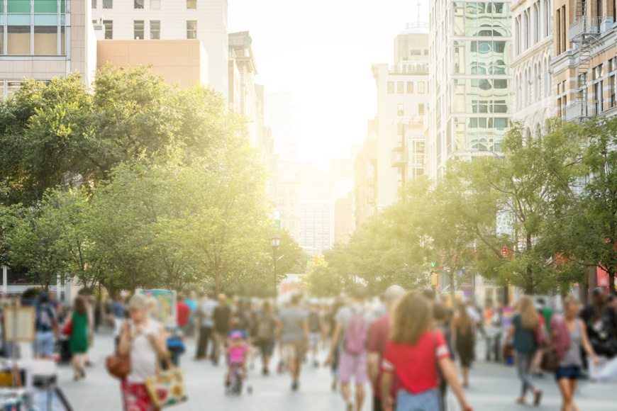 A blurred image shows a busy park in Manhattan with sunlight peeking through the buildings behind.