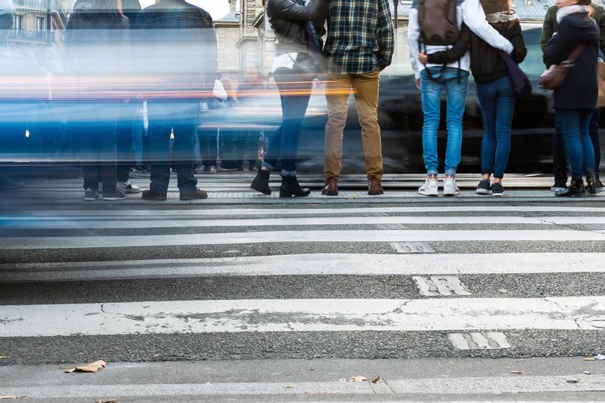 Personas esperan en un cruce peatonal en una calle de una ciudad mientras los autos borrosos pasan