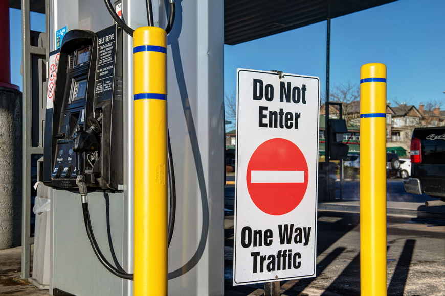 Two bright yellow bollard covers with blue stripes stand beside a No Entry sign near gas pumps