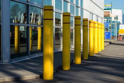 Yellow bollard sleeves cover bollards in front of a blue-windowed office building