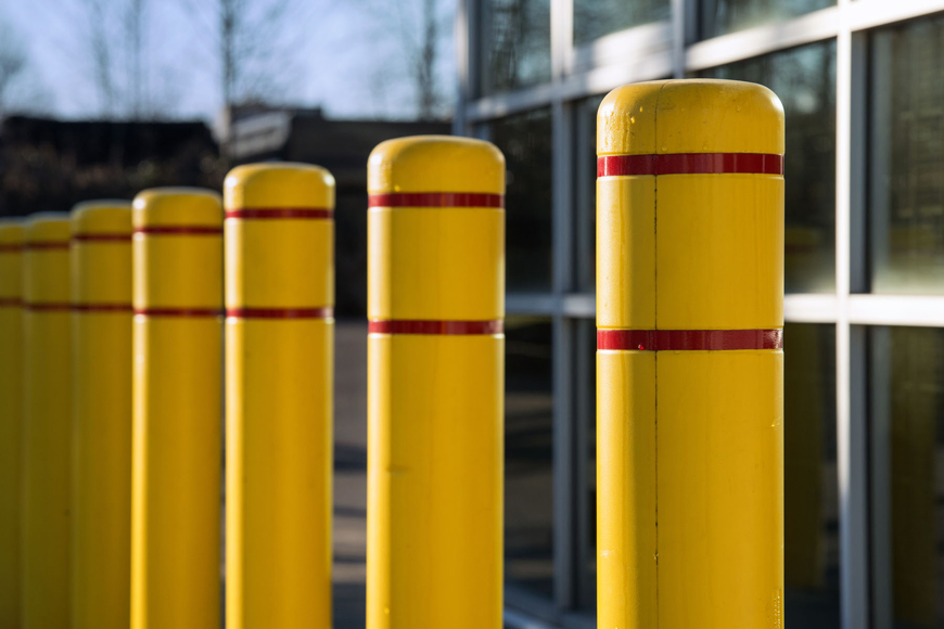 Yellow plastic bollard covers with red reflective tape line up in front of an office building