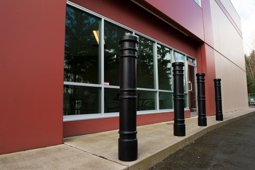 Four slender black bollards with three sets of decorative rings protect office building