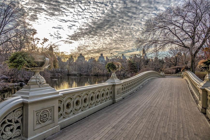 Un pont gris en fonte avec des fleurs et autres décorations, à Central Park