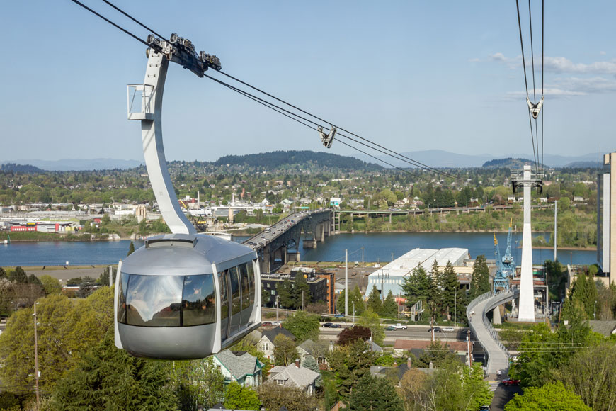 A tram on cables leading to Portland university sits in front of a sprawling, mostly one-and-two story city filled with trees.