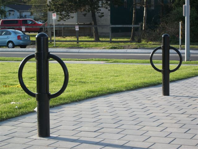 Two black outdoor bicycle racks of post and ring style stand on pavement beside a lawn