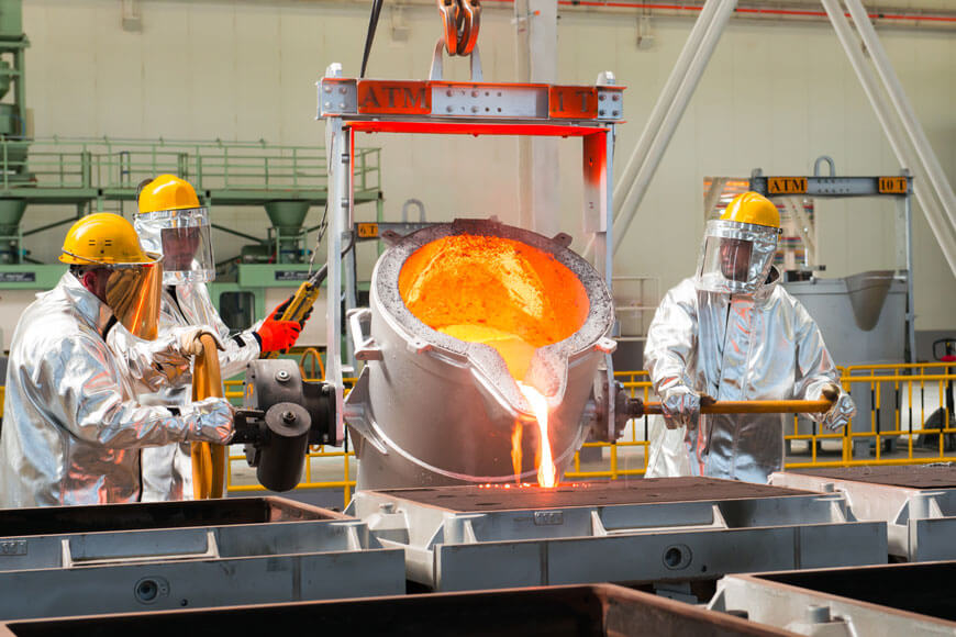 Workers in a modern foundry pouring metal into sand molds