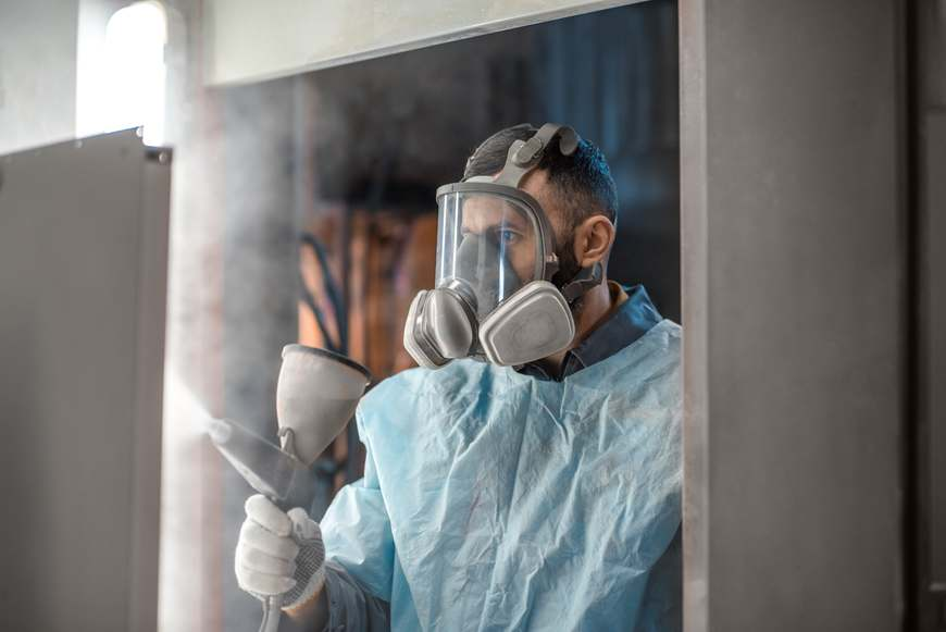 A worker in a mask and paper suit applies powder coat to aluminum in a factory