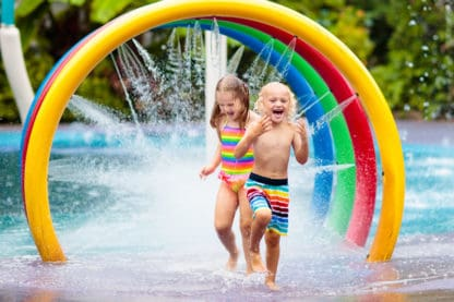 Two happy children play in water spray in a park filled with colorful bent tubes.