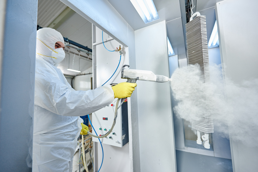 A man in coveralls and a mask shoots a stream of powder from a gun at a hanging metal item