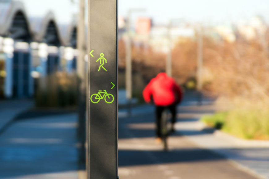 A square pole designates a bike path and walking path in the foreground; blurry cyclist in background