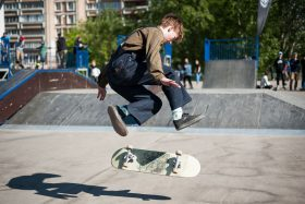 A boy wearing blue overalls and a striped shirt is caught mid-trick, hovering in the air above his turning board