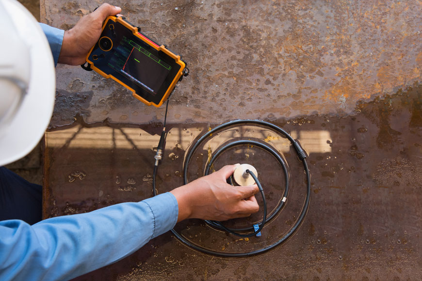 A technician uses a metal probe centered in a spiral of wire to test a wet, rusty metal surface