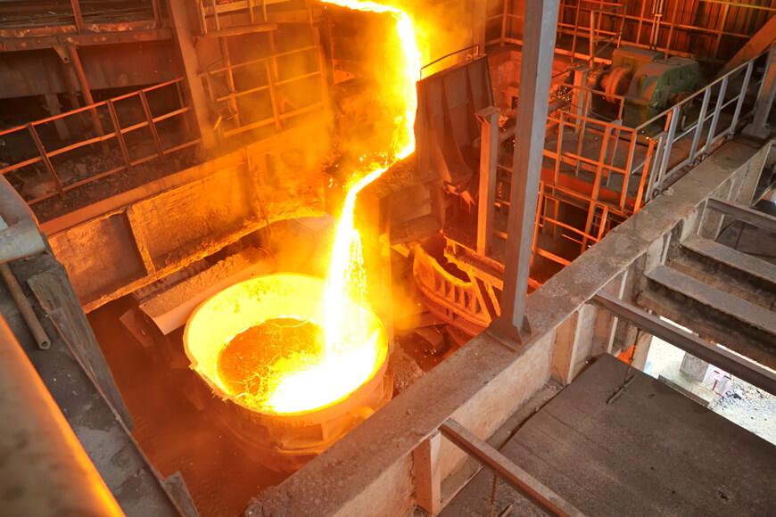 Metal siendo vertido de un horno fundidor a una cuchara de vertido