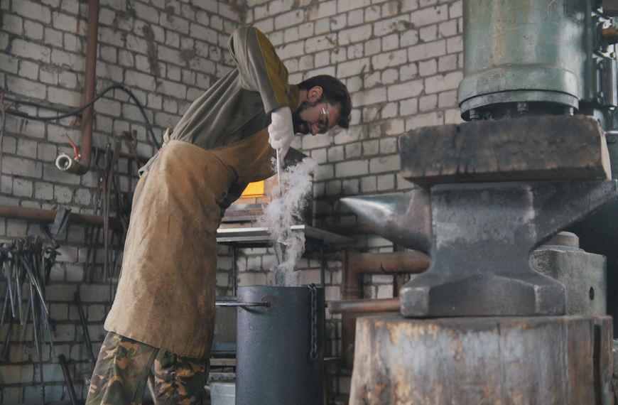 A bladesmith wearing safety clothing oil quenches his work before tempering it.