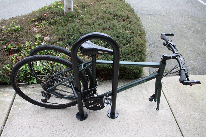 A green bike's front tire is removed and locked with the back tire to an outdoor bicycle rack