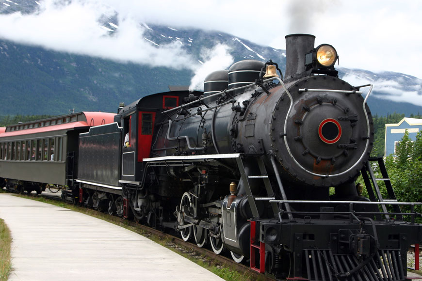 A steam train with steel wheels chugs past a mountain