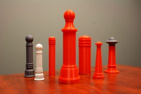 A series of small plastic model bollards in orange, white, or grey stand on a table