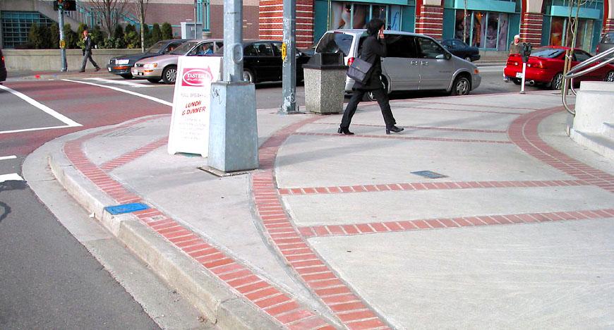 Pedestrians walk by sidewalk extensions