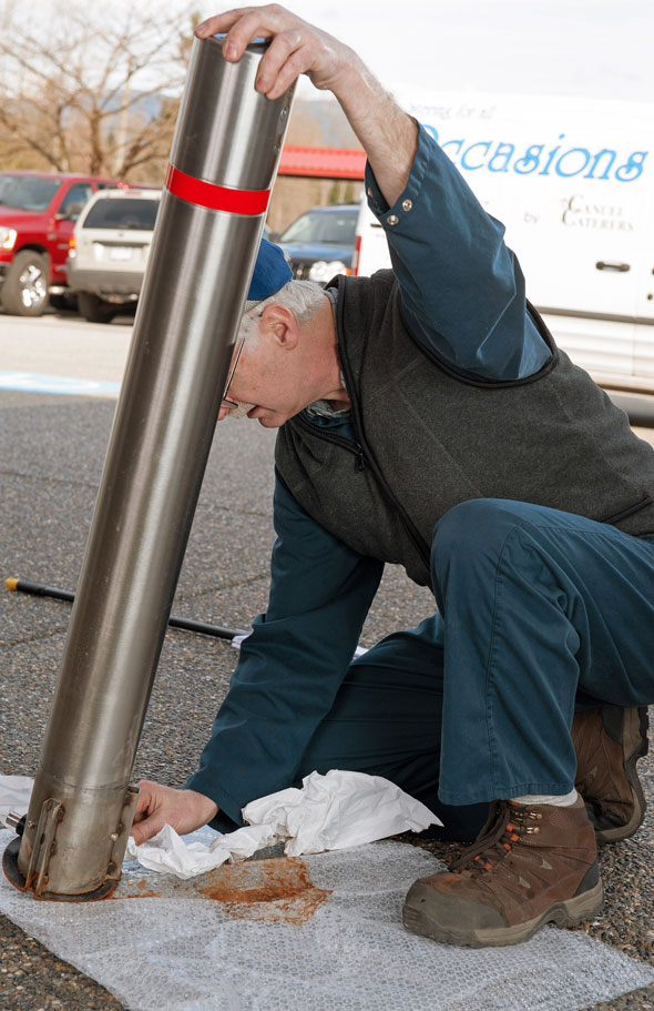 man installing stainless steel retractable bollard