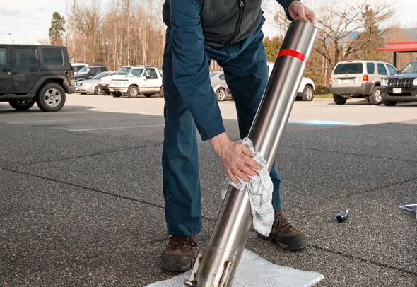 man cleaning stainless steel bollard