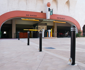 A line of padlocked removable bollards restrict access to a parking garage