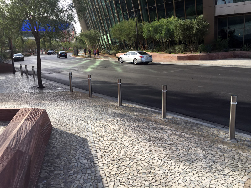A series of cylindrical stainless-steel retractable bollards in white cobblestone line a Vegas street
