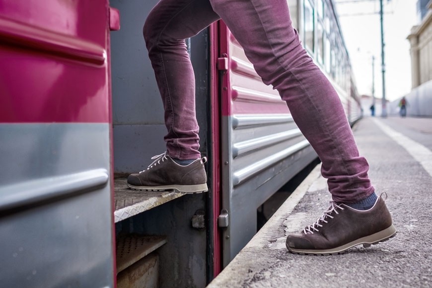 A close shot of a man's lower legs clad in purple jeans climbing on to a commuter train.