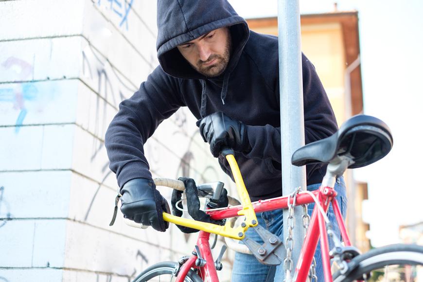 Un hombre corta el candando de cadena de una bicicleta pegada a una señal de calle