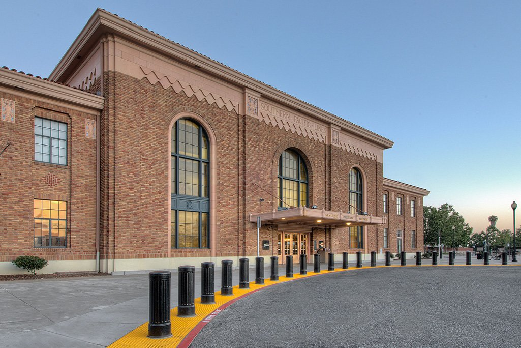 black bollards define a pedestrian drop-off zone in front of a red brick train station