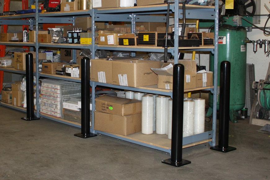 Bolt-down asset protecting bollards surround a warehouse shelving unit
