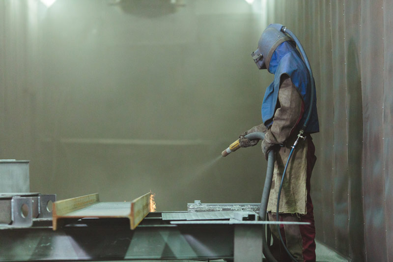 A worker covered in protective gear and mask aims a sandblaster at a piece of carbon steel