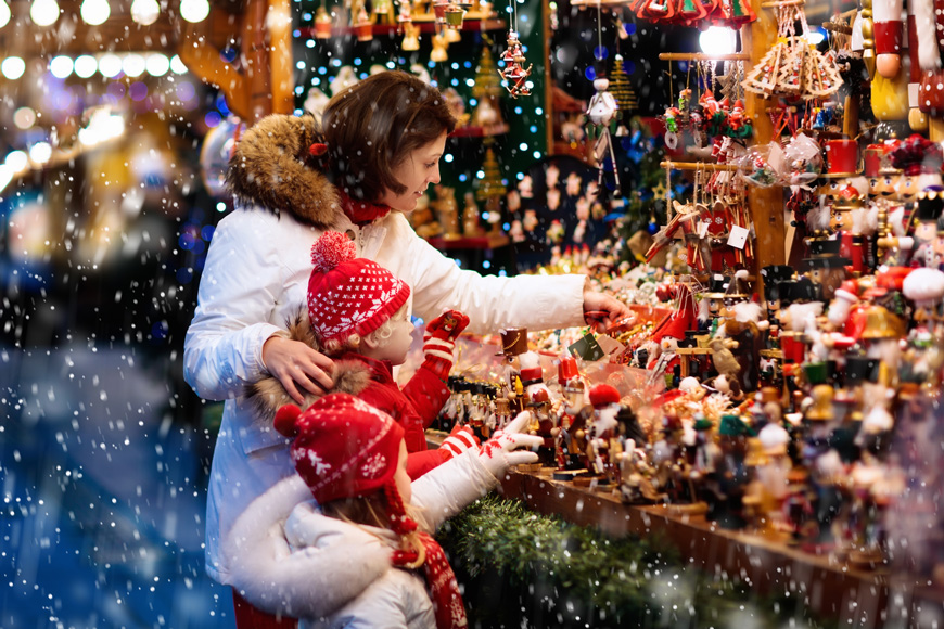 A mother and two children look at Christmas ornaments at a vendor in a snowy outdoor market.