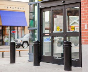 Modern black security bollards with ring decorations protect a storefront