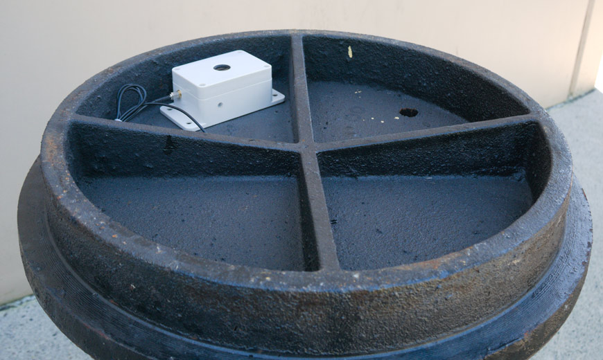 The underside of a manhole cover with a sensor installed