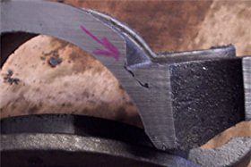 A cross section of a metal casting shows a crack that runs through the edge