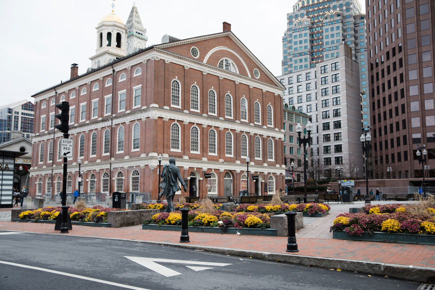 A brick building, Faneuil Hall, has a public square with benches and planters beside it