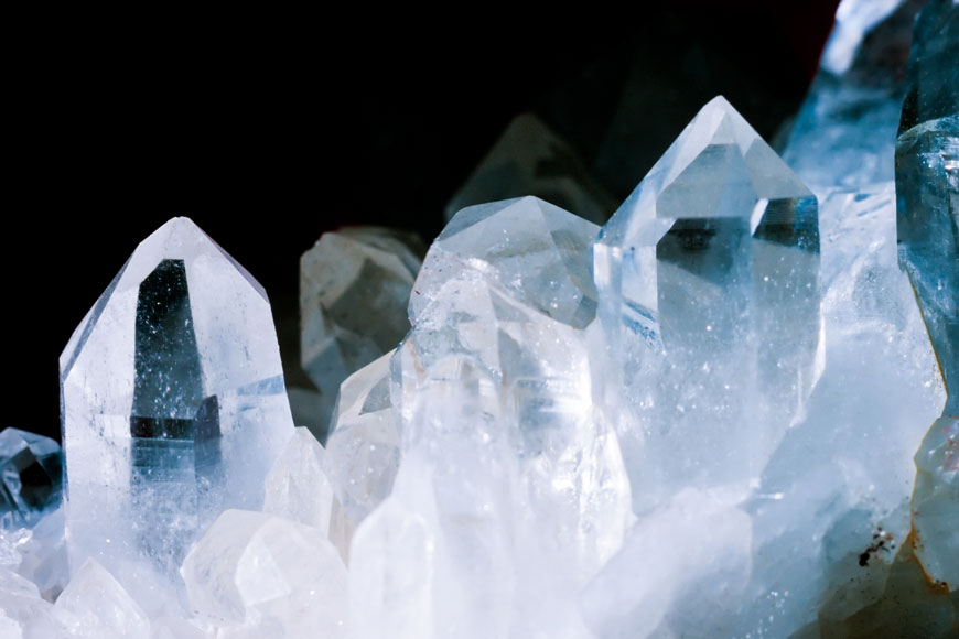 Crystalline plain clear quartz juts up in front of a black background