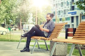 Man sits on urban park bench reading tablet, office buildings and trees behind him